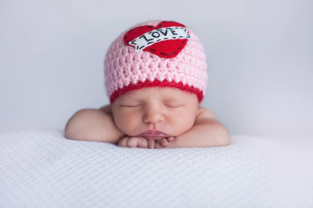 новорожденный в вязанной шапочке